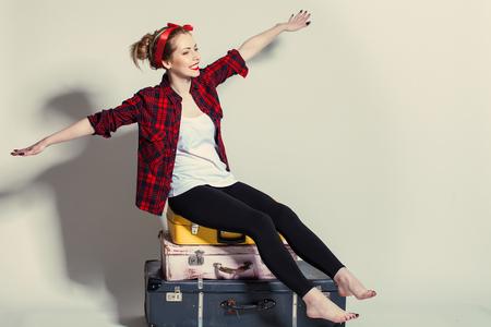 Photo pour woman sits on retro suitcases - image libre de droit