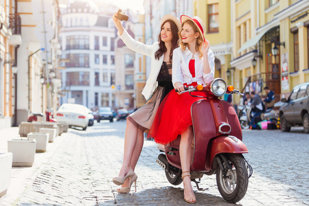 Foto per Two beautiful girls in urban background smiling with old scooter - Immagine Royalty Free