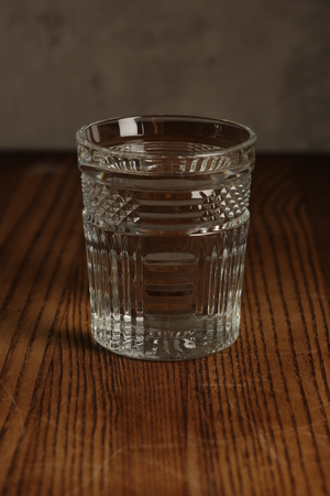Glass of water on a wooden table. Close up