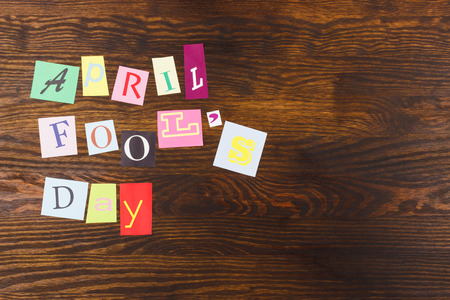 April fool's day: collage from colorful paper letters, wooden background