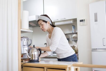 Photo for A woman cleaning the kitchen where she lives alone - Royalty Free Image