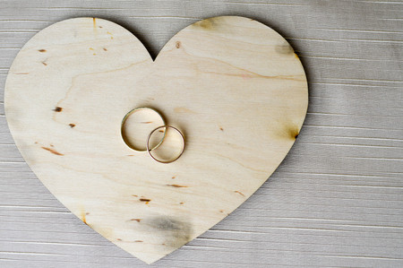 Gold wedding rings on a wooden heart. Bright, glittering, glamorous, fashionable, expensive hearts made of wood with adornments for Valentine's Day against a background of beige fabric.