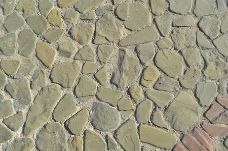 Photo for The texture of the stone road, pavement, walls of large gray old medieval round strong stones, cobblestones. The background. - Royalty Free Image