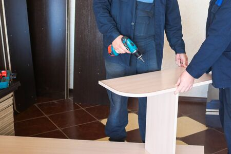 Photo pour A man worker in work clothes working with a screwdriver in his hands is assembling furniture. Professional repair in the apartment. - image libre de droit