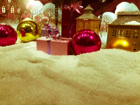 Photo for decoration for the showcase. round bright Christmas balls on artificial snow. next to gifts decorated with bright colored ribbons. - Royalty Free Image