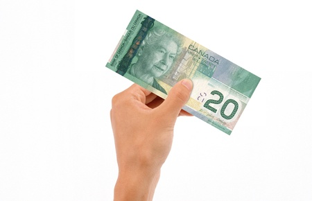 Hand holding 20 Canadian Dollar Bill islolated on white background.