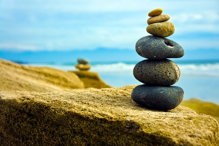 Foto de Zen Stone stacked together on blue coud background.  - Imagen libre de derechos