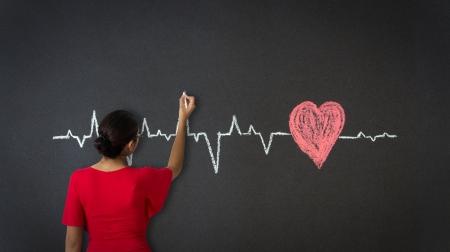 Photo pour Woman drawing a Heartbeat Diagram with chalk on a blackboard. - image libre de droit