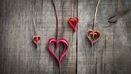 Hanging paper heart decoration on wood background.