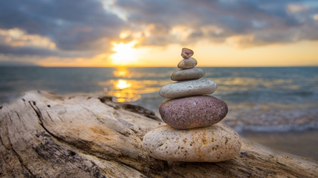 Photo pour Zen Stones on a tree trunk and sunset in the background. - image libre de droit