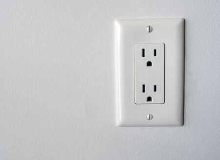 Photo for Isolated North American power outlet plug in socket on a white wall background Type B style - Royalty Free Image