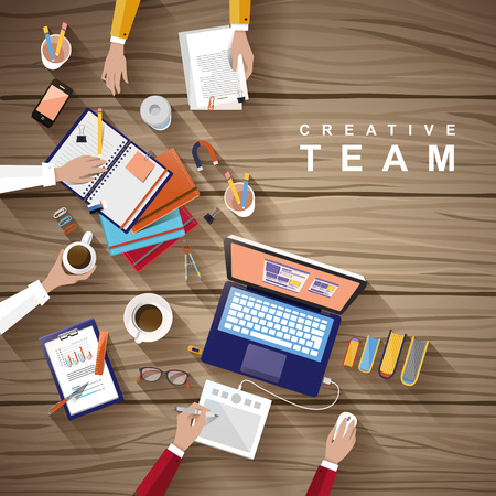 working place of creative team in flat design over wooden table