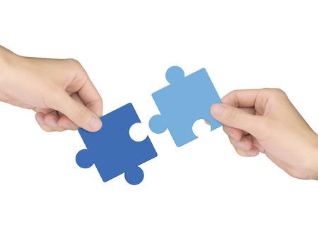Photo pour cooperation concept: hands holding jigsaw pieces over white background - image libre de droit