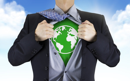 businessman showing earth icon underneath his shirt over blue skyの写真素材