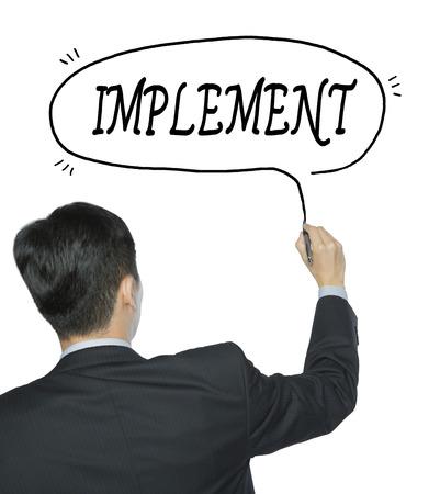 Photo pour implement written by businessman in black suit, hand writing on transparent board, photo - image libre de droit