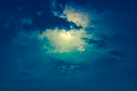 Background of nighttime sky with cloud and moon with shiny. Natural beauty at night with moon behind cloud. Cross process and vintage effect tone. The moon were NOT furnished by NASA.