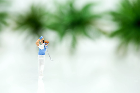 Miniature people : golfer stand with tree background.