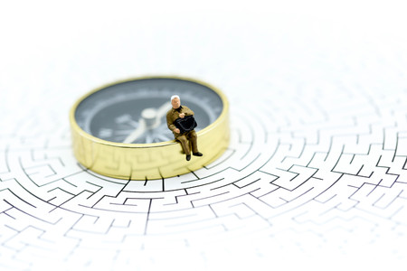 Miniature people : businessman sitting on compass with maze