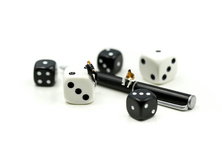 Miniature people : businessman standing with Black and white dices,Business competition Concept.