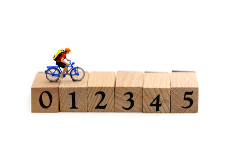 Miniature people : Travelers riding bicycle on wooden block number using as background traveling concepts.