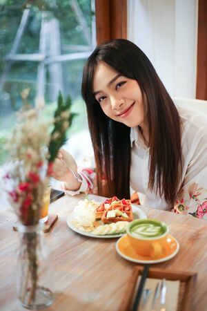 Photo for Beautiful asian woman eating delicious  waffles in coffee shop cafe. - Royalty Free Image