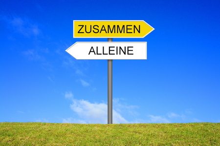 Signpost outside is showing Alone or together in german language