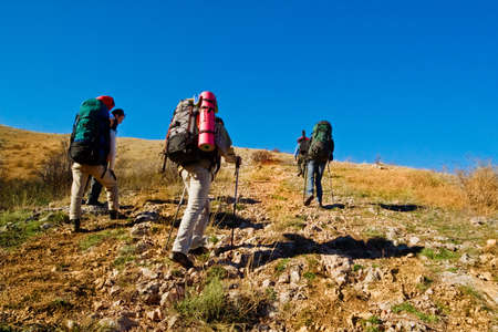 Group of hikers climbing up the rocky mountain