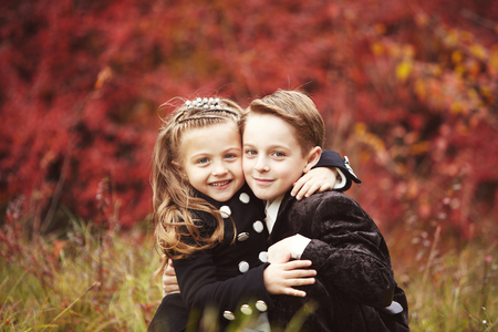 Little pretty girl and young boy huggind each other on autumn day. Brother and little sister cuddling. Happy family