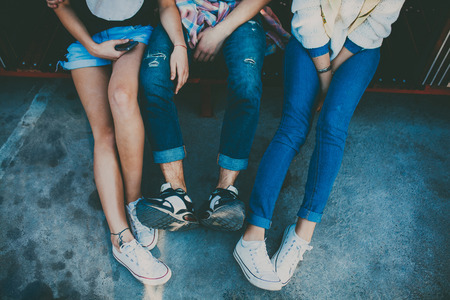 Photo pour Feet of three friends sitting together. Cropped portrait of two girl and one boy relaxing. Top view of shoes of hipsters resting. - image libre de droit
