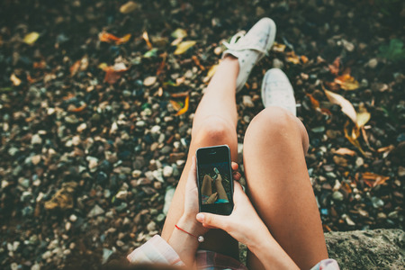 Teenage girl taking a selfie picture of her feet wearing white shoes on stony lakeside.