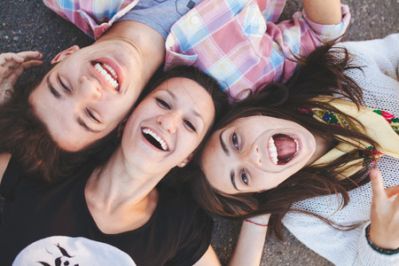 Foto de Closeup of three best friends lying down and laughing. Teenage people wearing casual clothes smiling. Top view - Imagen libre de derechos