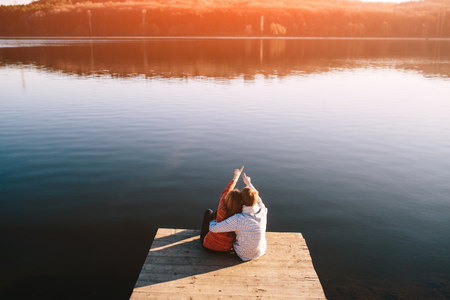 Foto de A young teenagers couple dreaming on the wooden jetty at a lake - Imagen libre de derechos