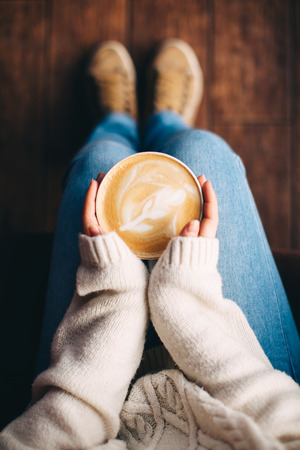 Photo pour Close up of girl's hands holding a cup of coffee indoors. Top view and feet - image libre de droit