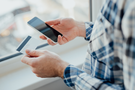 Photo pour Man's hands holding a credit card and using smart phone for online shopping - image libre de droit