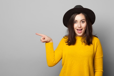 Photo pour smiling young woman pointing finger away isolated on a grey background - image libre de droit