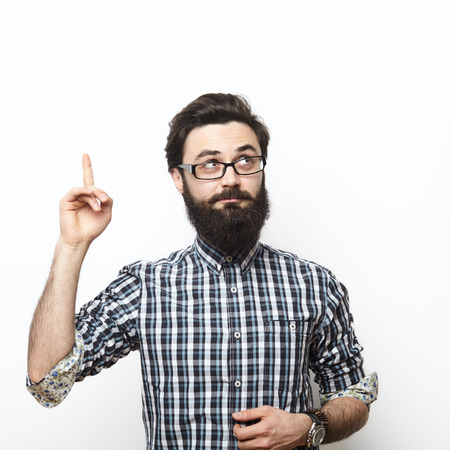 Photo for Casual man looking up and pointing his finger to blank space over white background. I have an Idea concept - Royalty Free Image