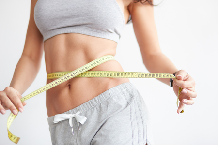 Photo pour Woman measuring her waistline. Closeup of female with perfect slim body and torso. Healthy nutrition and weight losing concept. - image libre de droit