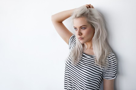 Photo pour beautiful young blond woman posing while leaning on white wall with copy space. Hipster girl with blue eyes and bleached silver hair - image libre de droit