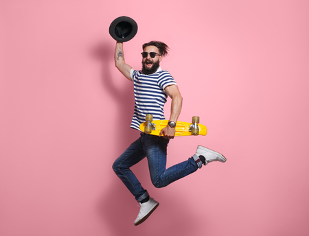 Photo pour Hipster man jumping with longboard - image libre de droit