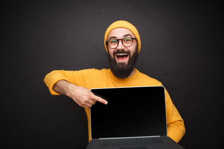 Photo for Smiling man pointing at laptop - Royalty Free Image
