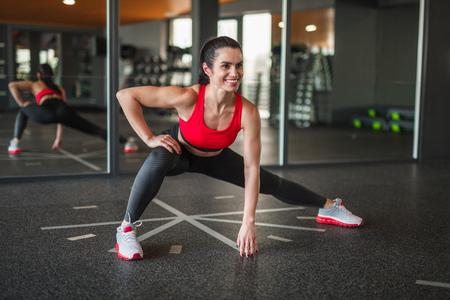 Photo pour Cheerful sportive woman doing side lunges - image libre de droit