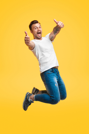 Photo pour Excited man jumping and gesturing thumb up - image libre de droit