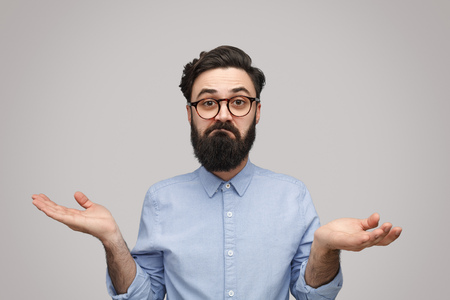 Foto de Doubtful bearded man shrugging with shoulders - Imagen libre de derechos
