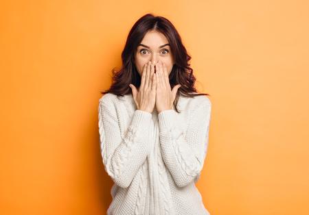 Photo pour amazed young woman over orange background - image libre de droit