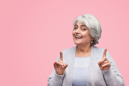Photo for Cheerful senior female pointing up - Royalty Free Image