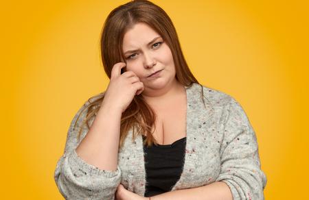 Photo pour Thoughtful plump woman scratching face - image libre de droit