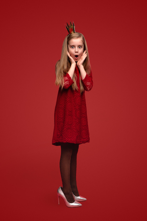 Photo for Shocked little princess in adult shoes - Royalty Free Image