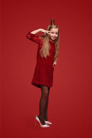 Foto de Little princess in stiletto shoes gesturing V sign - Imagen libre de derechos