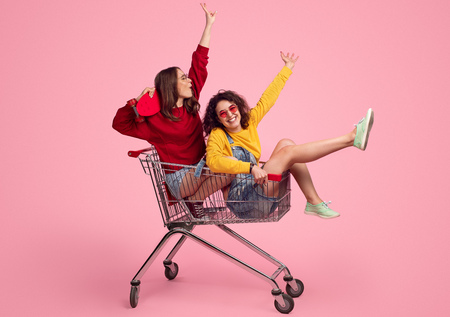 Foto de Young hipsters riding shopping cart - Imagen libre de derechos