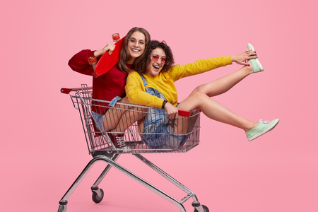 Photo for Cheerful hipsters riding shopping trolley - Royalty Free Image